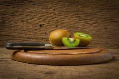 Киви Отрезанный половинно свеже разделочная доска с ножом на старой древесине стоковая фотография rf