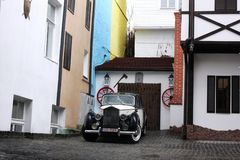 Киев, Украина; 10-ое апреля 2014 Старые автомобили на предпосылке старых зданий в английском стиле стоковое фото
