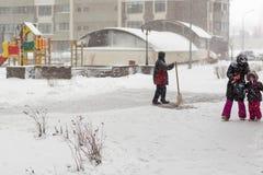 КИЕВ, УКРАИНА - 18-ОЕ ДЕКАБРЯ 2017: Работник очищает дорожку на дворе жилого дома во время сильных снегопадов Стоковая Фотография RF
