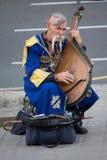 Киев, Украина - 19-ое июня 2016: Пожилое kobzar в национальном костюме играет kobza Стоковые Фото