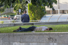 Киев, Украина - 19-ое июня 2016: Пьяный человек спать на лужайке дальше Стоковая Фотография RF