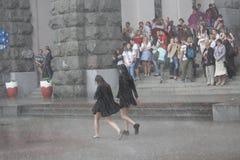 Киев, Украина - 27-ое мая 2016: Девушки идут без зонтика в лить дожде Стоковые Фото