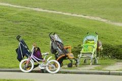 Киев Украина - 2-ое мая 2018: Различные детские дорожные коляски и велосипед на backgroung зеленой травы стоковая фотография rf