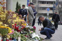 КИЕВ, УКРАИНА - 14-ое ноября 2015: Люди кладут цветки на французское посольство в Киеве в памяти о терактах жертв в Pari Стоковые Изображения
