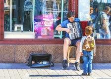 Киев, Украина - 22-ое сентября 2018: Мальчик fascinated путем играть на аккордеоне музыканта улицы на Khreshchatyk стоковая фотография