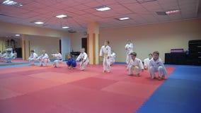 КИЕВ, УКРАИНА - 6-ое февраля 2017: Дети в кимоно делают физические упражнения на тренировке карате акции видеоматериалы