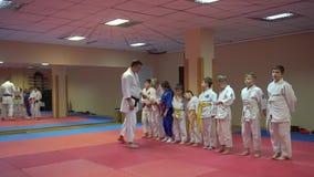 КИЕВ, УКРАИНА - 6-ое февраля 2017: Тренировка карате и тренер помогают ребенк правильно одеть кимоно и пояс видеоматериал