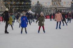 Киев Украина - 01 01 2018: счастливые люди катаясь на коньках на катке на зимних отдыхах стоковое фото rf