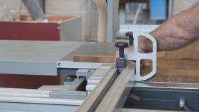 Киев UA, 30-05-2019 Мужской плотник работая на круговой машине в мастерской, работник режа деревянную планку на предмете мебели акции видеоматериалы