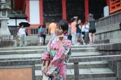 Кимоно женщин вывешивают и усмехаются для фото внутри святыня Fushimi Inari в Киото, Японии Селективный фокус на wowen Стоковые Фотографии RF