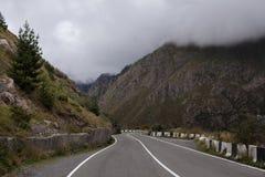 Кинематографический ландшафт дороги Throuth дороги асфальта горы С пасмурным небом Стоковое Изображение
