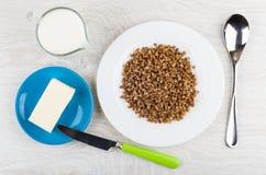 Кипеть гречиха в плите, кувшине молока, масла в поддоннике Стоковая Фотография