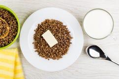 Кипеть гречиха с маслом, чашкой молока, салфеткой и ложкой Стоковое Фото