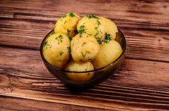 Кипеть молодые картошки в стеклянном шаре на деревянном столе стоковое изображение rf