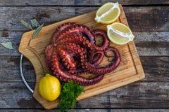 Кипеть осьминог готовый для подачи с лимоном и петрушкой на деревянной доске Стоковые Фото