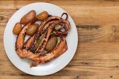 Кипеть осьминог с картошкой на белой плите Стоковая Фотография