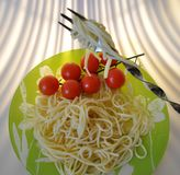 Кипеть спагетти на зеленой плите с томатами и базиликом Стоковые Изображения
