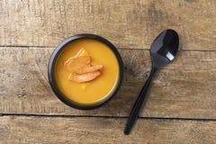 Кипеть суп тыквы в пищевом контейнере с черной ложкой, готовой едой, который нужно съесть стоковое изображение rf