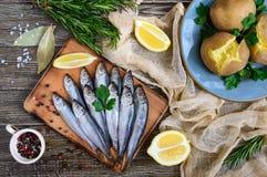 Кипеть unpeeled картошки в кожах, малая посоленная рыба прибалтийских сельдей, шпротин на деревянном столе Стоковое Фото