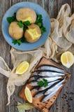 Кипеть unpeeled картошки в кожах, малая посоленная рыба прибалтийских сельдей, шпротин на деревянном столе Стоковое фото RF