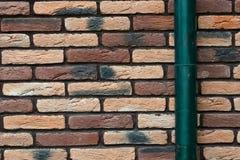 Кирпичная стена и водосточная труба как предпосылка Стоковые Фото