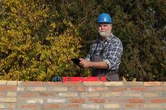 Кирпичная стена работника рассматривая, используя таблетку Стоковые Фотографии RF