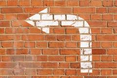 Кирпичная стена с знаком направления стоковое изображение