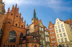 Кирпичное здание суда Artus, фасад красивых типичных красочных домов со шпилем городской ратуши и предпосылкой голубого неба башн стоковое фото