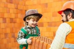 Кирпич Команда построителей Построение нового дома Отец и сын на строительной площадке стоковая фотография