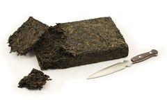 Кирпич чая pu-erh сломанный (изолированным) ножом Стоковая Фотография