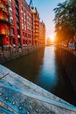 Кирпич Touristic пятна старый красный осветил здания, канал и квадрат в золотом свете захода солнца speicherstadt hamburg стоковая фотография
