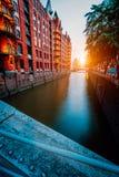 Кирпич Touristic пятна старый красный осветил здания, канал и квадрат в золотом свете захода солнца speicherstadt hamburg стоковые фото