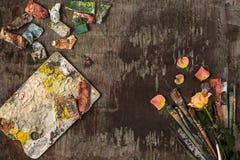 Кисти и трубки красок масла на деревянной предпосылке Стоковое Фото