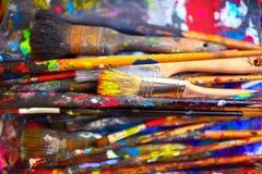 Кисти различных размеров, запятнанные яркими цветами, конец стоковые изображения