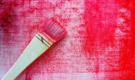 Кисть с красным цветом на холсте стоковая фотография rf