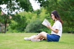 Китайская девушка читая книгу на траве Стоковые Фотографии RF