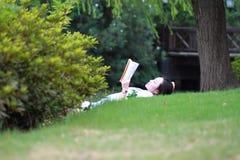 Китайская девушка читая книгу Белокурая красивая молодая женщина при книга лежа на траве Стоковые Изображения RF