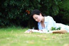 Китайская девушка читая книгу Белокурая красивая молодая женщина при книга лежа на траве Стоковая Фотография RF