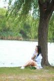 Китайская девушка читая книгу под деревом Белокурая красивая молодая женщина с книгой сидит на траве Стоковое фото RF