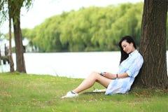 Китайская девушка читая книгу под деревом Белокурая красивая молодая женщина с книгой сидит на траве Стоковая Фотография RF