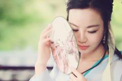 Китайская женщина в традиционной игре платья Hanfu в саде Стоковые Изображения