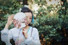 Китайская женщина в традиционной игре платья Hanfu в саде Стоковые Изображения RF
