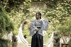 Китайская женщина в традиционном голубом и белом платье Hanfu стоя в середине красивого строба стоковые фото