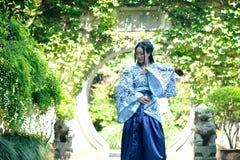 Китайская женщина в традиционном голубом и белом платье Hanfu стоя в середине красивого строба стоковые изображения