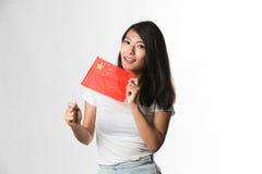 Китайская женщина задерживая китайский флаг против белой предпосылки стоковые фото