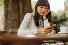 Китайская женщина с мобильным телефоном на внешнем кафе Стоковые Фотографии RF