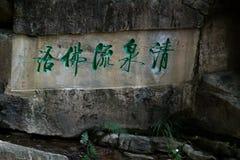 Китайская каллиграфия высекаенная на утесе над заводью стоковое изображение