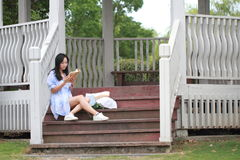 Китайская книга чтения девушки Белокурая красивая молодая женщина с книгой сидит на шагах павильона Стоковое фото RF