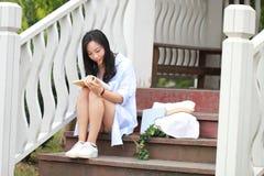 Китайская книга чтения девушки Белокурая красивая молодая женщина с книгой сидит на шагах павильона Стоковое Фото