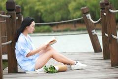 Китайская книга чтения девушки Белокурая красивая молодая женщина с книгой сидит на мосте около загородки Стоковая Фотография